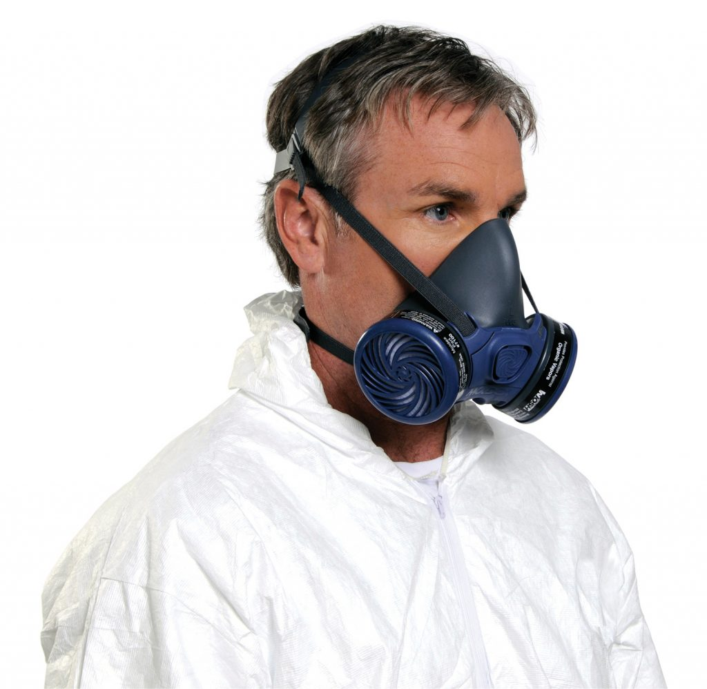 man shows how to wear blue and black half-face reusable respirator mask