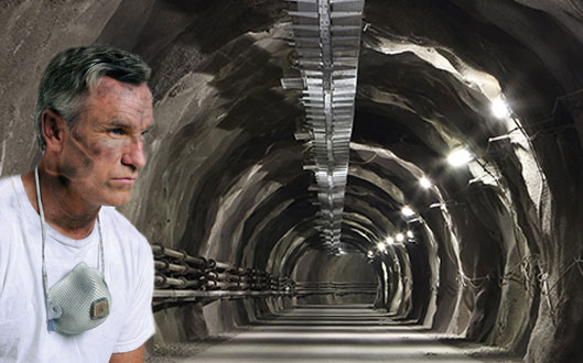 man standing in front of tunnel with face mask around neck